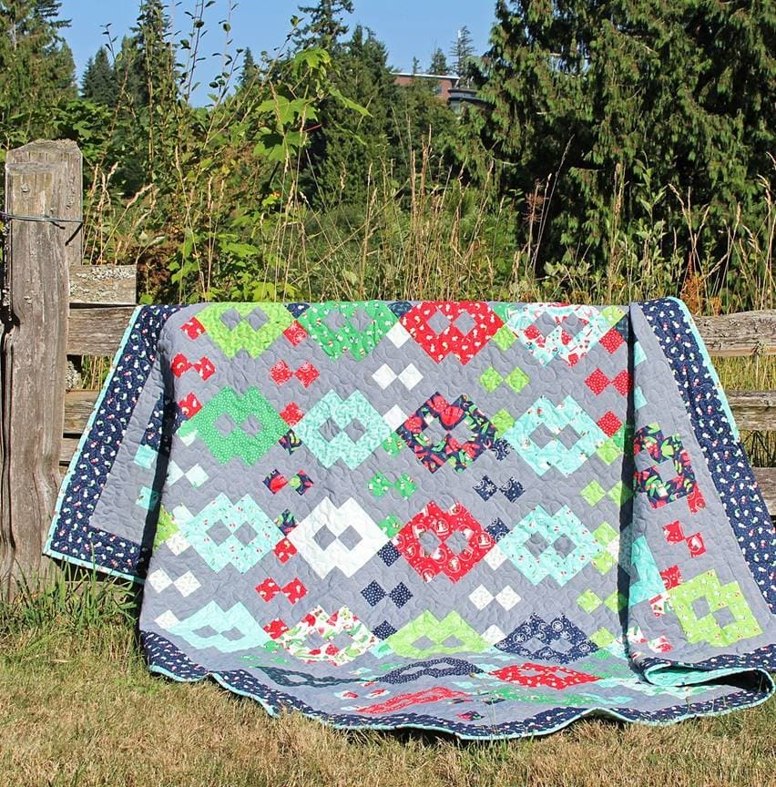 Large quilt draped over a fence