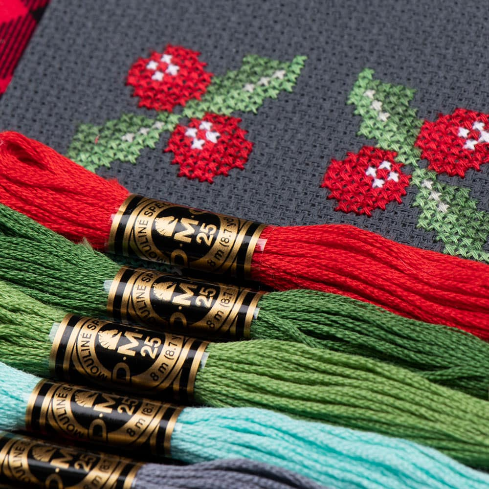 The first row of the mystery All the Trimmings cross stitch piece is revealed under red, green, and blue floss. They are multiple stitched Holly leaves.