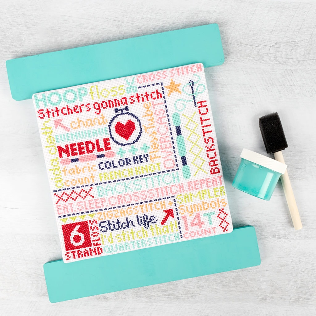The Stitch-O-Graphy sampler is laying next to a tin of Kitchen Cupboard Chalky Chicks Paint and a paint brush!
